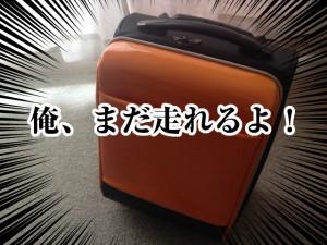 傷だらけのオレンジのスーツケース